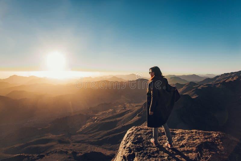 De vrouw bevindt zich op rand van klip op Onderstel Sinai tegen achtergrond van zonsopgang stock fotografie