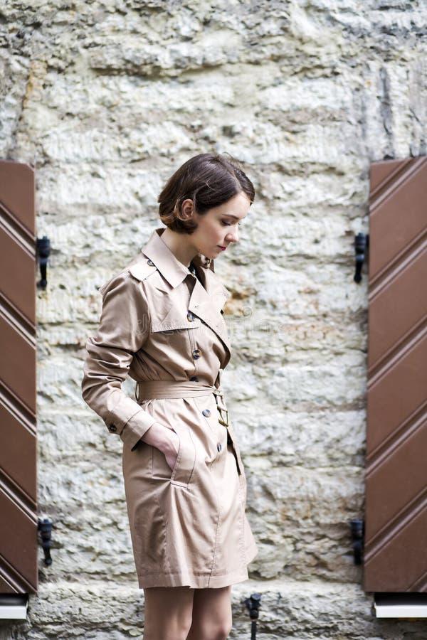 De vrouw bij beige laag met handtas keek neer royalty-vrije stock afbeelding