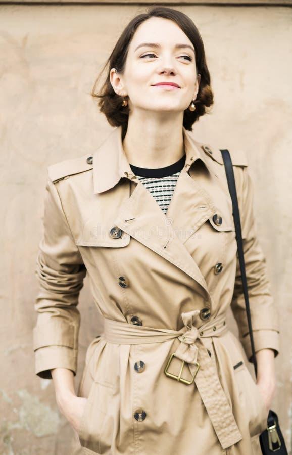 De vrouw bij beige laag met handtasglimlach neemt heimelijk royalty-vrije stock afbeeldingen