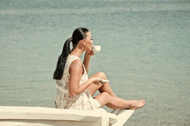 De vrouw bij de oceaan drinkt koffie Overzees of oceaan en drinkende vrouw stock fotografie