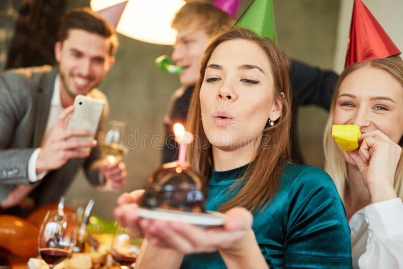 De vrouw blaast uit cake op verjaardagspartij royalty-vrije stock foto's