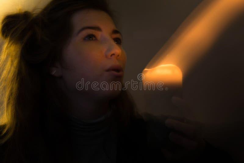 De vrouw blaast uit een magische kaars stock afbeeldingen