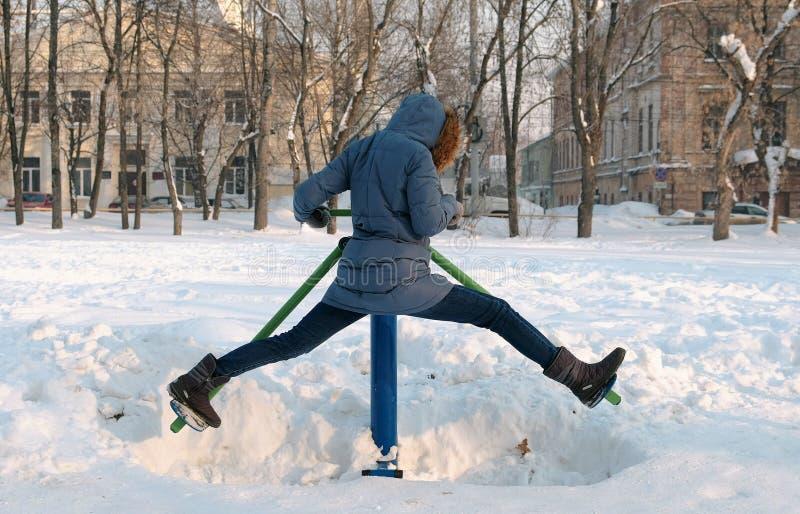 De vrouw in blauw benedenjasje met een kap doet benenoefeningen op simulator in een de winterpark in stads Achtermening stock foto's