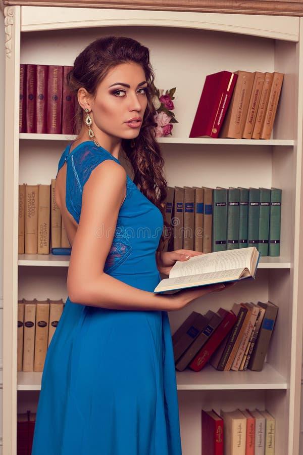 De vrouw in blauw opent terug kleding met het boek van de kantlezing romantisch stock foto's