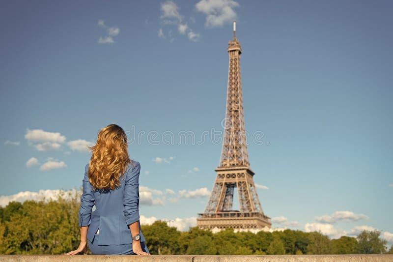 De vrouw in blauwe kleding bekijkt de toren van Eiffel in Parijs, Frankrijk, manier Vrouw met lang haar, kapsel, achtermening, sc stock fotografie