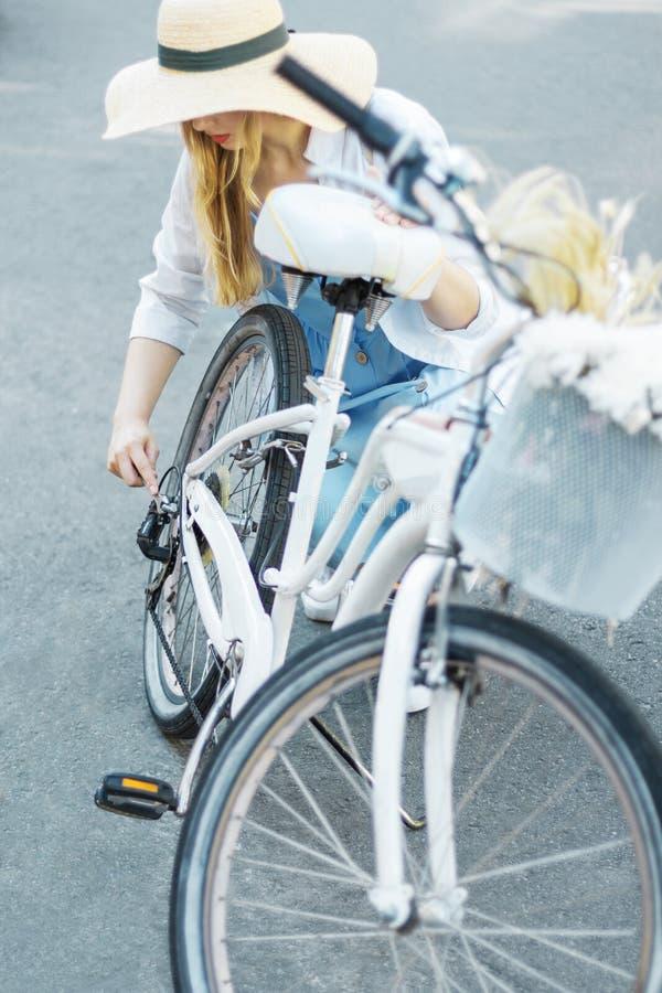 De vrouw in blauwe kleding en strohoed herstelt witte vrouwelijke fiets royalty-vrije stock fotografie