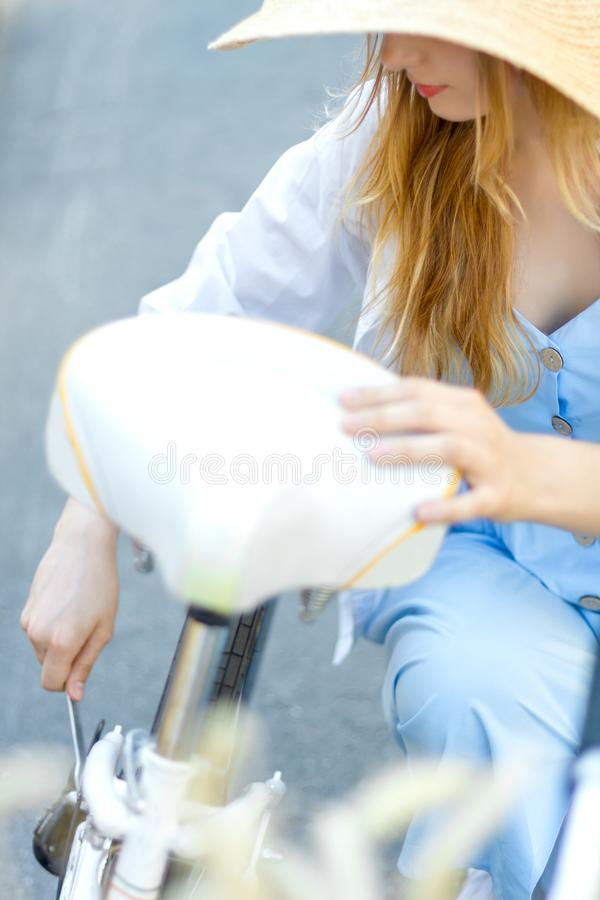De vrouw in blauwe kleding en strohoed herstelt witte vrouwelijke fiets royalty-vrije stock foto's