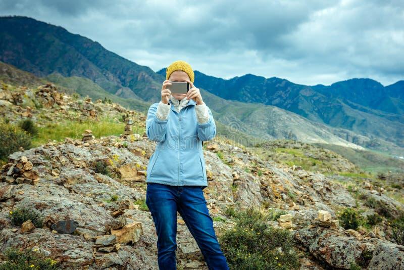 De vrouw blogger stijgt foto en video door smartphone op de achtergrond van bergen en bewolkte hemel op Reizende levensstijl stock foto