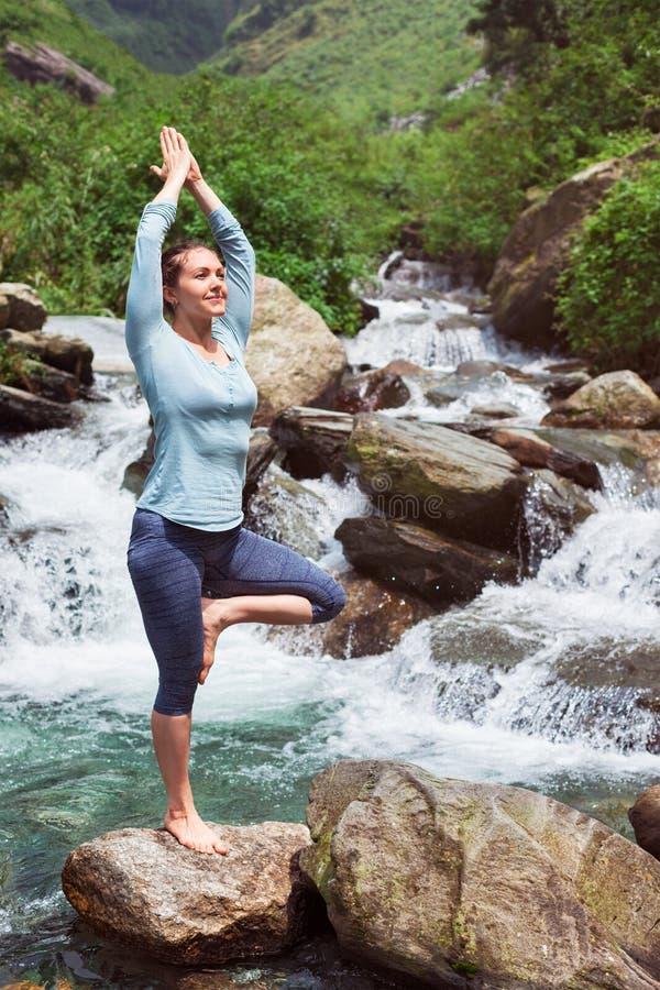 De vrouw in de boom van Vrikshasana van yogaasana stelt in openlucht bij waterval stock foto
