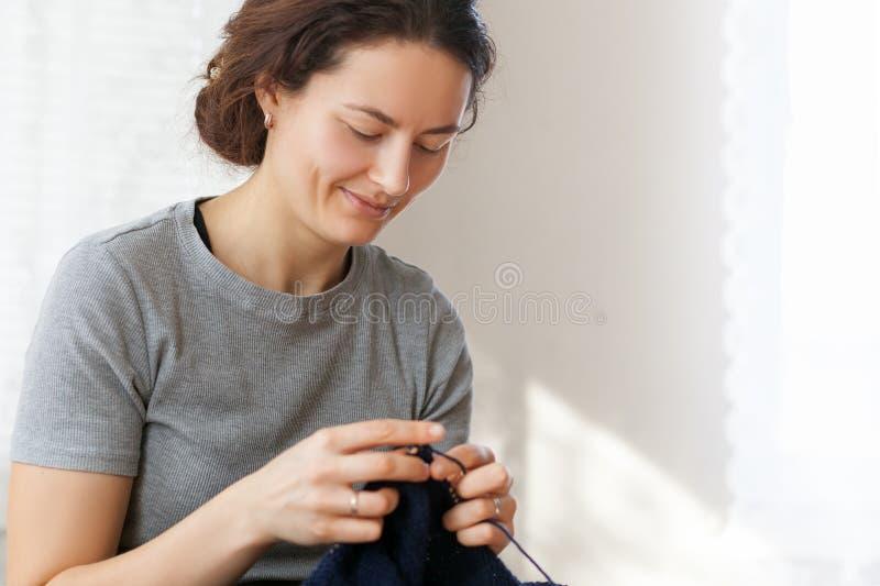De vrouw breit met een breiende sweater stock foto's