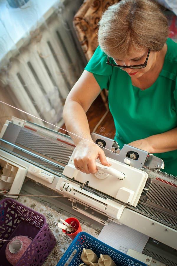 De vrouw breit op een breiende machine, stock foto