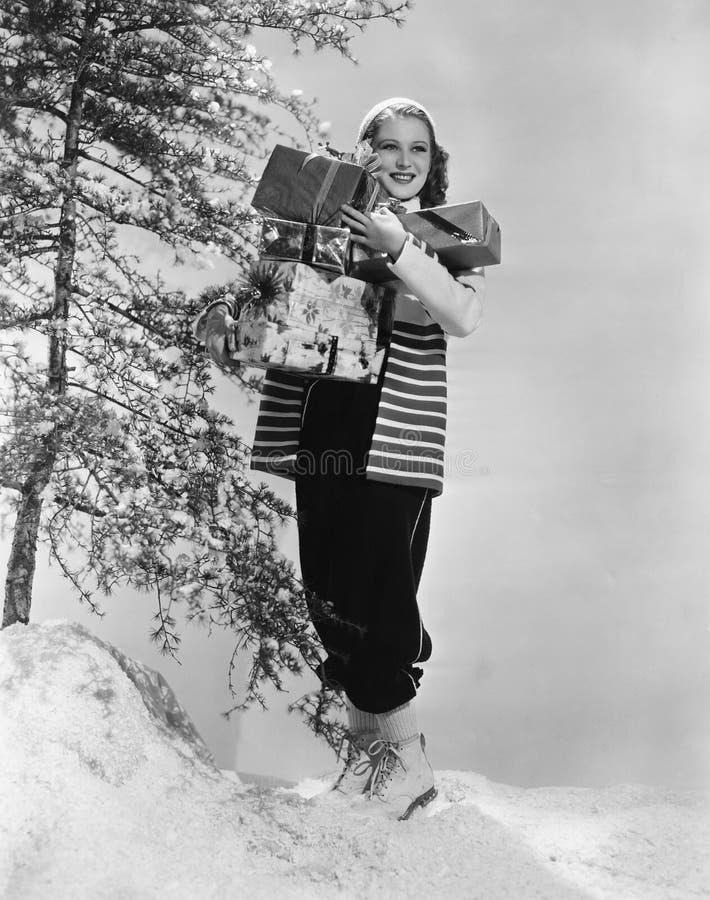 De vrouw buiten in sneeuw met Kerstmis stelt voor (Alle afgeschilderde personen leven niet langer en geen landgoed bestaat Levera royalty-vrije stock fotografie