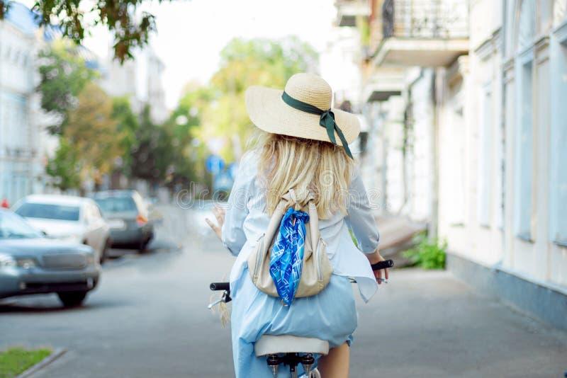 De vrouw cirkelt in blauwe kleding op fiets op lege stadsstraat stock fotografie