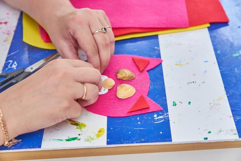De vrouw creeert een kat van rood en overzeese shells op de workshop wordt gevoeld die royalty-vrije stock fotografie