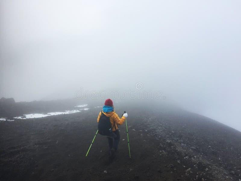 De vrouw daalt de vulkaanhelling stock foto's