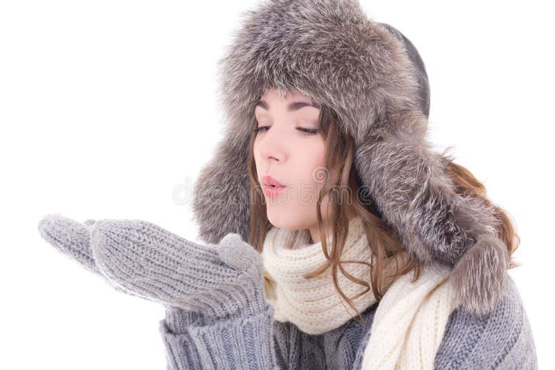 De vrouw in de winterkleren die iets van haar palmen blazen isoleert stock foto's
