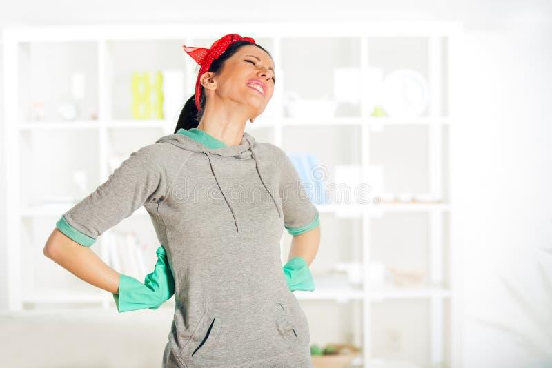 De vrouw deed terug pijn terwijl het schoonmaken royalty-vrije stock afbeeldingen