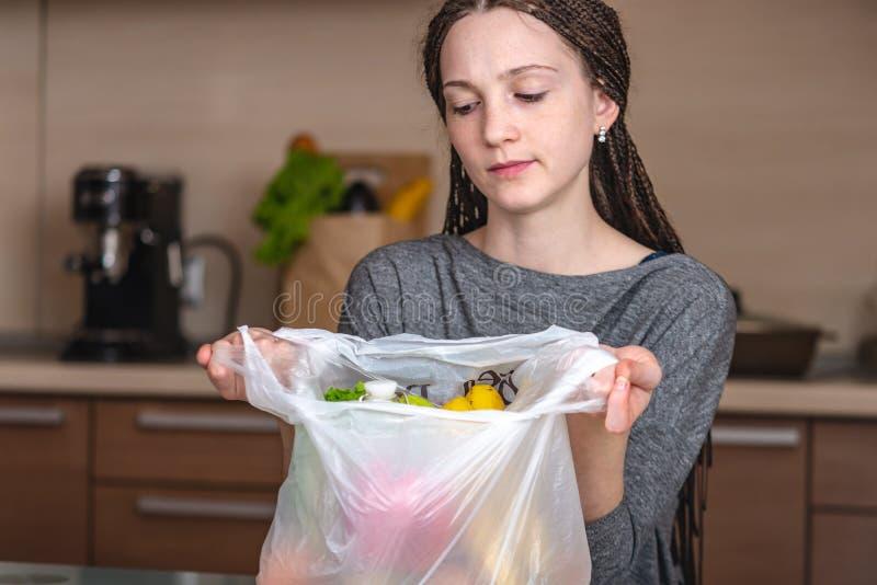 De vrouw denkt dat afval om een plastic zak te gebruiken om producten te kopen Milieubescherming en het verlaten van plastiek stock fotografie