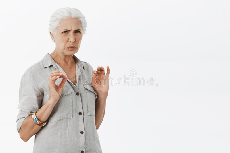 De vrouw denkt het doend walgen Portret van ontstemde hogere vrouw met wit haar en het grimassen trekken griezelig zien die frons stock fotografie