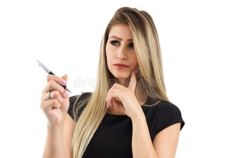 De vrouw denkt over wat zij gaat schrijven Blondeperso stock afbeelding
