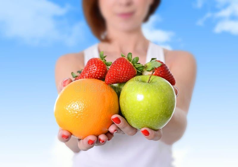 De vrouw die appel, oranje fruit en aardbeien tonen dient concept van de dieet binnen het gezonde voeding in stock foto's