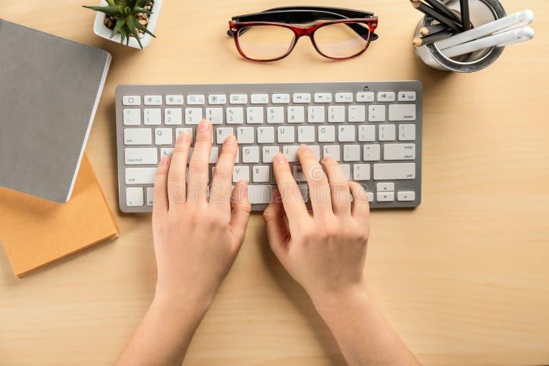 De vrouw die computer met behulp van bij lijst, vlakte lag Werkplaatssamenstelling royalty-vrije stock fotografie