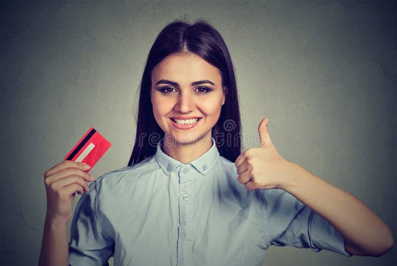 De vrouw die creditcard het geven houden beduimelt omhoog royalty-vrije stock foto
