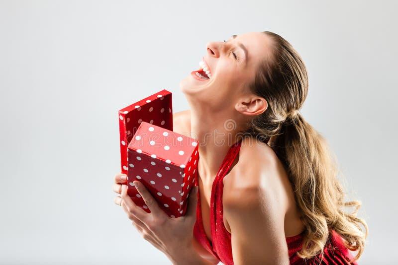 De vrouw die de gift openen en is gelukkig royalty-vrije stock fotografie