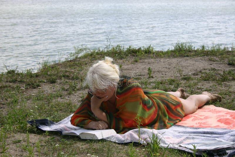 De vrouw die een rust heeft dichtbij water stock fotografie