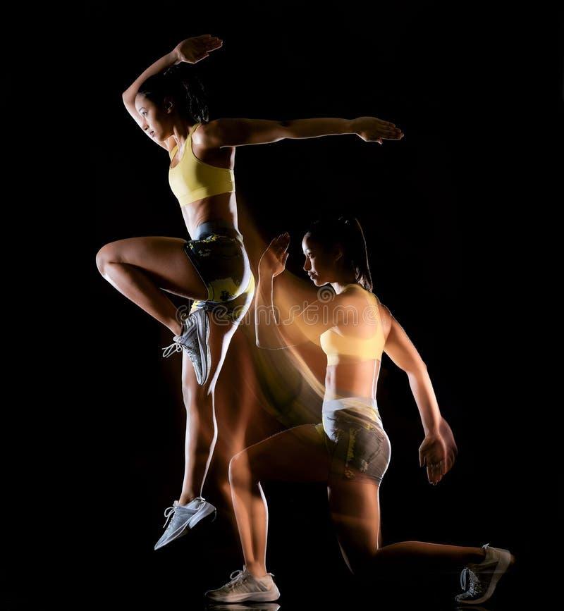 De vrouw die geschiktheidsoefeningen uitoefenen isoleerde zwart lightpainting effect als achtergrond stock foto's