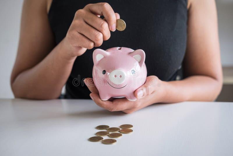 De vrouw die gouden muntstuk in roze spaarvarken zetten voor voert groeiende zaken aan winst en het sparen met spaarvarken op, Be royalty-vrije stock afbeelding