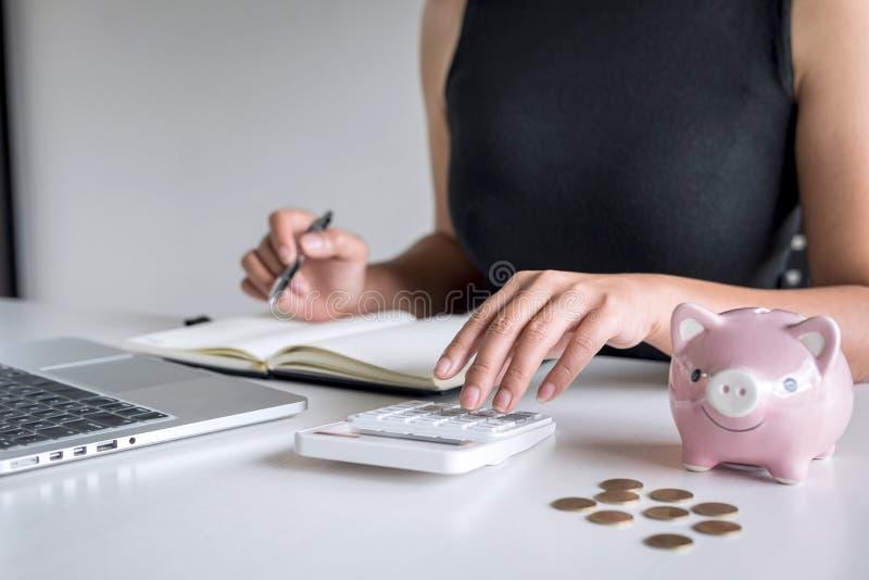 De vrouw die gouden muntstuk in roze spaarvarken zetten voor voert groeiende zaken aan winst en het sparen met spaarvarken op, Be stock fotografie
