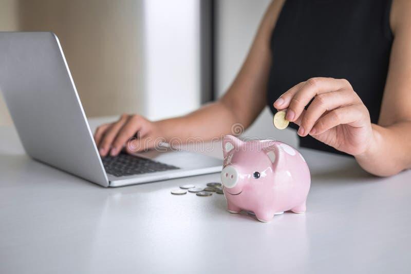 De vrouw die gouden muntstuk in roze spaarvarken zetten voor voert groeiende zaken aan winst en het sparen met spaarvarken op, Be stock afbeelding
