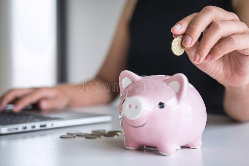 De vrouw die gouden muntstuk in roze spaarvarken zetten voor voert groeiende zaken aan winst en het sparen met spaarvarken op, Be royalty-vrije stock afbeeldingen