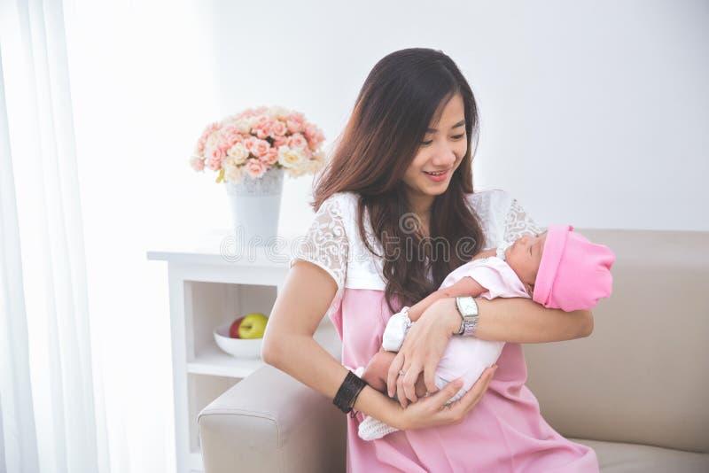 De vrouw die haar babymeisje houden, sluit omhoog stock foto