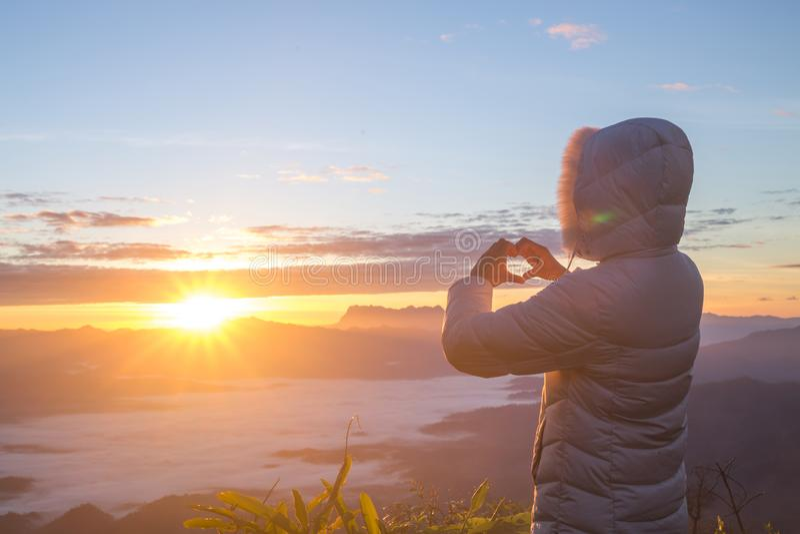 De vrouw die hartvorm maken tijdens zonstijging, God is liefdeconcept, Hartvorm, Bergtoerisme, Symbool van liefde, de manifestati stock foto