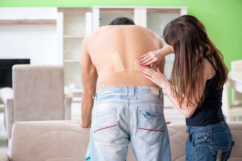 De vrouw die het pleister van het pepercapsicum toepassen op echtgenoot om pijn te verlichten royalty-vrije stock foto