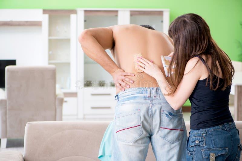 De vrouw die het pleister van het pepercapsicum toepassen op echtgenoot om pijn te verlichten stock foto's