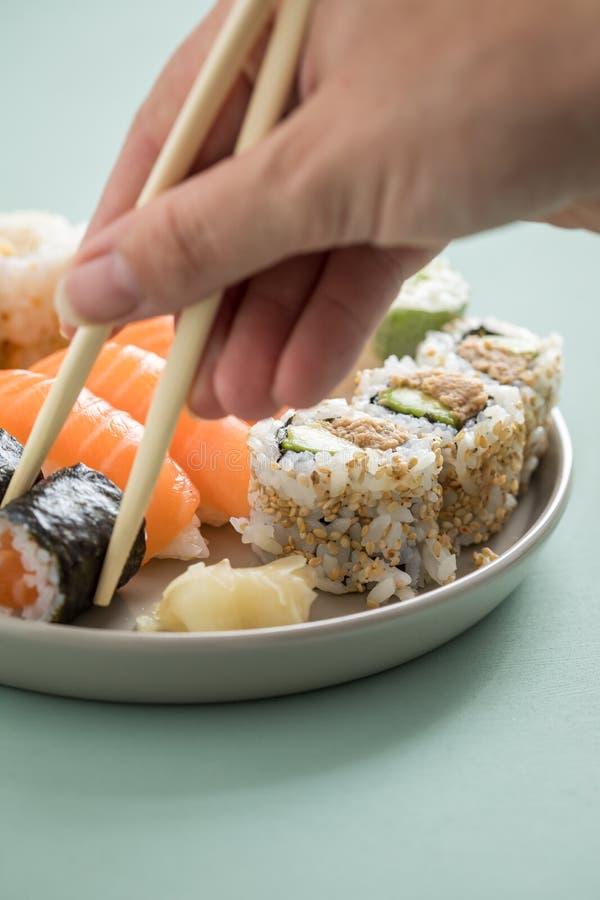 De vrouw die Japanse tonijnavocado Californië met zalm Nigiri en Maki van sushi eten mengt binnenstebuiten plaat met houten eets royalty-vrije stock afbeelding