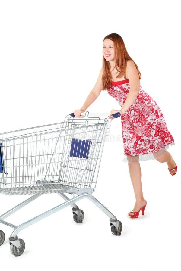 De vrouw die kleding draagt beweegt het winkelen mand. stock foto
