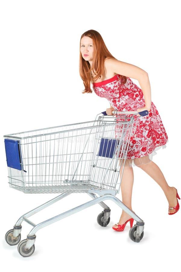 De vrouw die kleding draagt beweegt het winkelen mand stock afbeelding