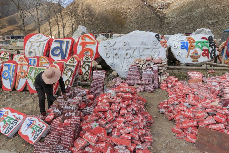 De vrouw die Mani-stenen met boeddhistische mantra Om Mani Padme Hum verkopen graveerde in Tibetaans in Yushu, China royalty-vrije stock fotografie