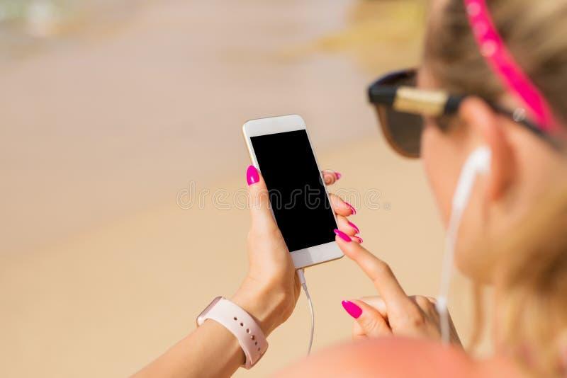 De vrouw die mobiele telefoon met behulp van en luistert in openlucht aan muziek stock foto's