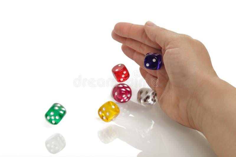 De vrouw die ??n of andere kleurrijk werpen dobbelt met haar die handen op witte achtergrond worden ge?soleerd Het gokken, casino stock foto's