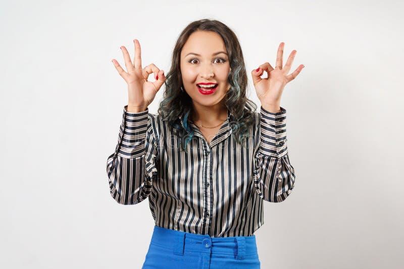 De vrouw die O.K. teken met allebei tonen dient de Studio, op een wit in stock foto