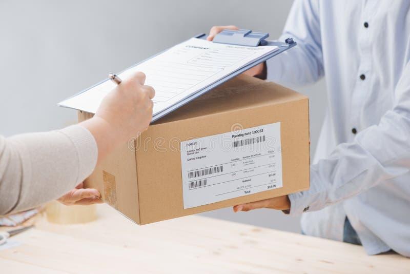 De vrouw die ontvangstbewijs van leveringspakket ondertekenen, sluit omhoog stock foto's