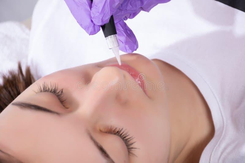 De vrouw die permanent heeft maakt omhoog of tatoegering op haar lippen in schoonheidssalon met professioneel instrument stock afbeelding