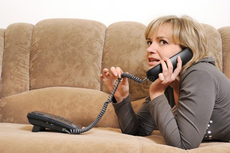 De vrouw die telefonisch op een bank spreekt stock afbeelding