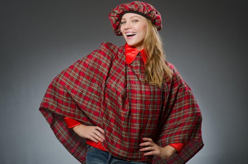 De vrouw die traditionele Schotse kleding dragen stock afbeelding
