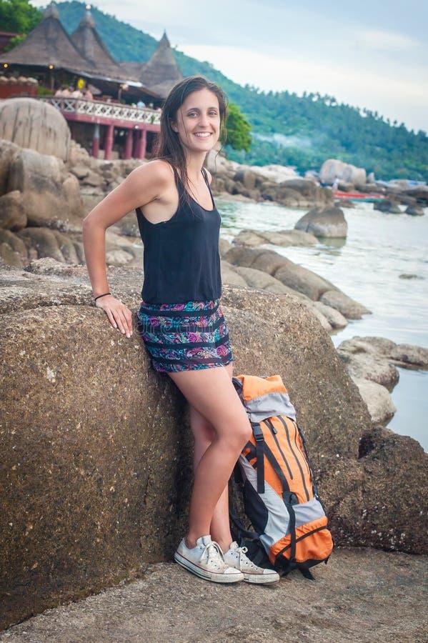 De vrouw die van de avonturenreiziger backpacker op rots bij zonnig strand ontspannen royalty-vrije stock afbeelding
